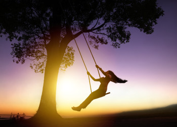 Happy -Woman-On-A-Swing With Sunset Backgroun